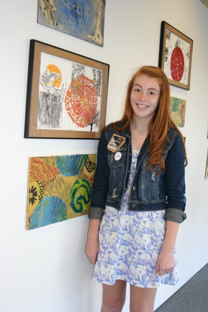 Student Kate Koning stands next to her artwork at the GRAM.